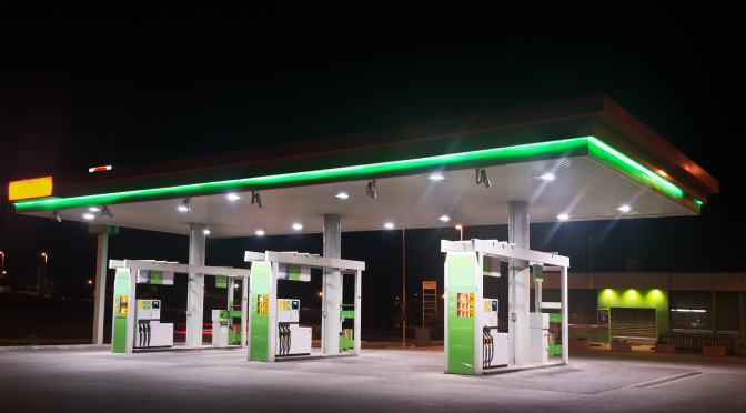 green and white gas station by night